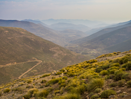 Landscape view of dangerous and curvy mountain dirt road with steep drop to the valley and sheep, Lesotho, Africa