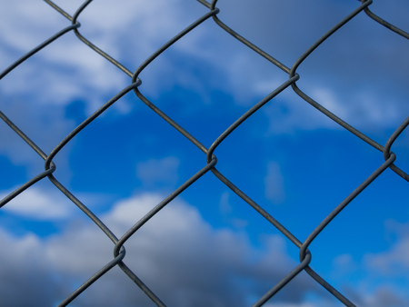 Closeup of metal chainlink fence in front of dramatic blue cloudy sky Stock Photo