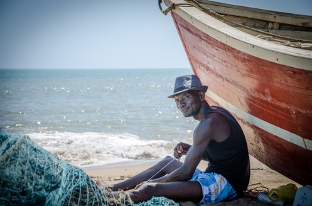 LOBITO, ANGOLA - 9. MAI 2014: Nicht identifizierter angolanischer Fischer, der vor rotem Fischerboot an den Strandfestlegungsnetzen sitzt Standard-Bild - 89803461