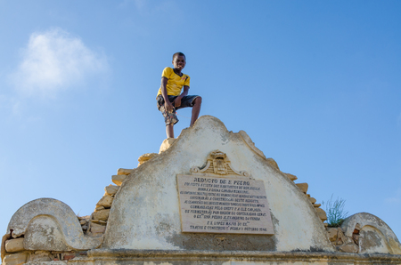 LOBITO, ANGOLA - MAY 09 2014: Unidentified African boy with yellow shirt standing on Reducto Sao Pedro Portuguese fort