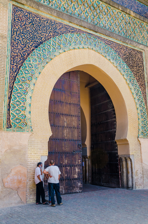Meknes, Morocco - August 21 2013: Three unidentified Moroccan men talking in front of historic Bab Mansour Gate