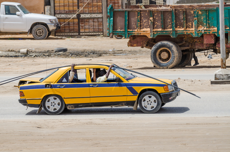 Nouakchott, Mauritania - October 08 2013: Street scene with steel rods transported by old taxi Editorial