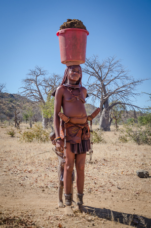 Young Himba or Muhimba tribe woman balancing bucket of clay on head