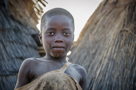 Boy of the Tata Somba tribe or Tammari people with torn clothes standing on roof of mud building Editoriali