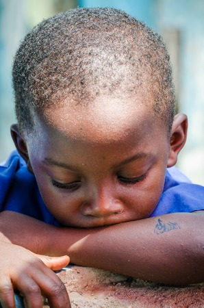 Portrait of unidentified young African boy looking down