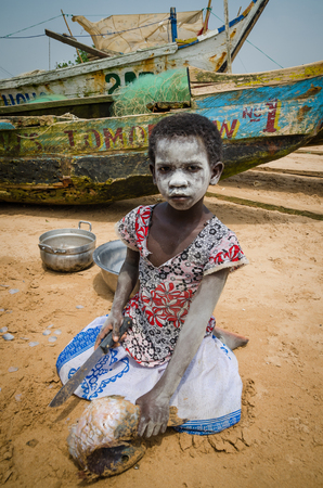 Unidentified young African girl with white painted face cutting fish with machete at beach