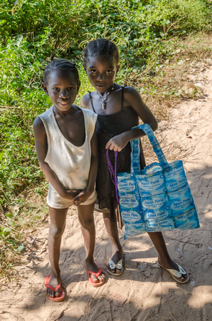 Bubaque, Guinea Bissau - December 07, 2013: Portrait of two unidentified young African girls in dresses on dirt path