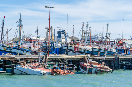 Luderitz, Namibia - July 08 2014: Luderitz harbor with many fishing boats and one sunken shipwreck Editorial