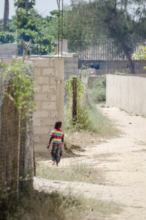 Saint-Louis, Senegal - October 20, 2013: Unidentified young African boy with colorful shirt walking through sandy street Editorial
