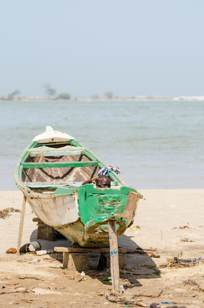 Saint-Louis, Senegal - October 20, 2013: Unidentified young African boy hiding in wooden boat and waving Editorial