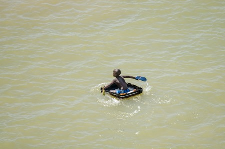 Saint-Louis, Senegal - October 20, 2013: Unidentified African boy using suitcase as boat and paddling with sandals