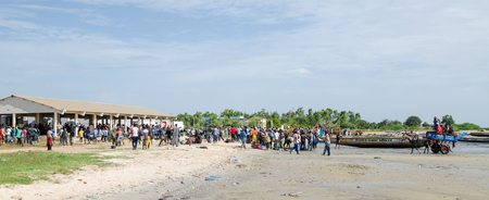 Many people on beach with fish market and fishing boats, return of the fishermen