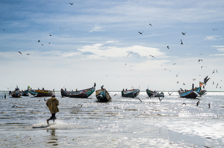 Unidentified fisherman running in water to traditional painted wooden fishing boat Editorial