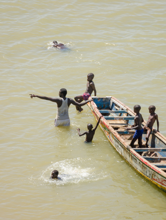 Saint-Louis, Senegal - October 20, 2013: Unidentified African children and grown man swimming next to wooden boat
