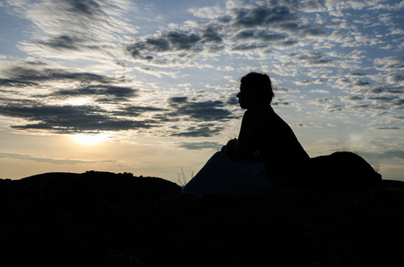 Silhouette of young woman sitting on top of rocks of Pedras Negras or Pungo Andongo during sunset, Angola, Africa Banco de Imagens - 114114118
