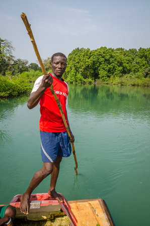 Tokeh Beach, Sierra Leone - January 06, 2014: Unidentified African man pushing simple raft on mangrove river with stick