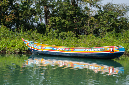 Tokeh Beach, Sierra Leone - January 06, 2014: Beautiful and colorful painted wooden dugout boat moored in mangroves