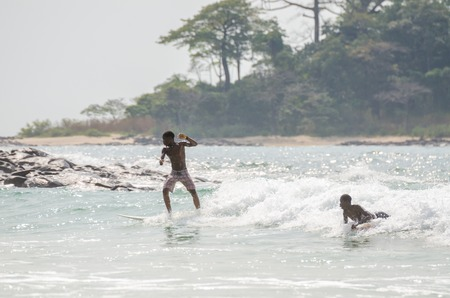 Bureh Beach, Sierra Leone - January 11, 2014: Two unidentified young African boys surfing at only surf spot in country Redakční