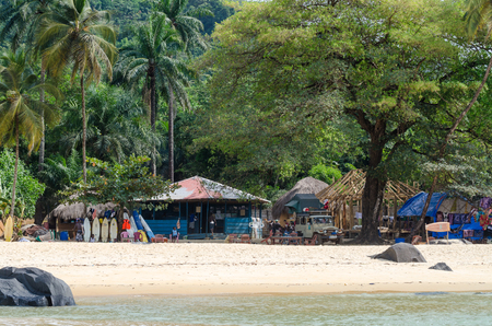 Bureh Beach, Sierra Leone - January 11, 2014: Bureh Beach surf club with colorful buildings, surf boards and trees Redakční