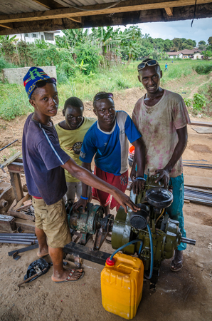 Bo, Sierra Leone - January 19, 2014: Group of unidentified young African mechanics operating diesel generator
