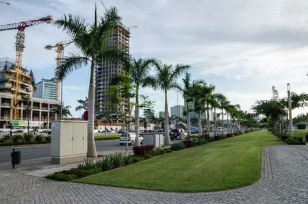 Luanda, Angola - April 28 2014: Luandas promenade with palms and construction of modern high rise buildings at sea side