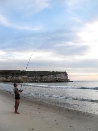 Luanda, Angola - April 26, 2014: Recreational young fisherman standing at beach north of Luanda angling, Angola, Africa
