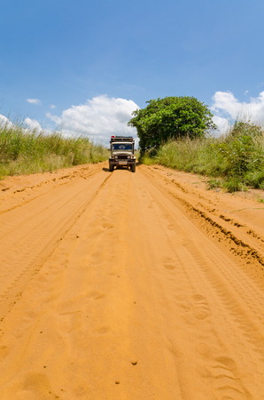 Vintage 4x4 car driving on sandy red dirt road in countryside of Democratic Republic of Congo