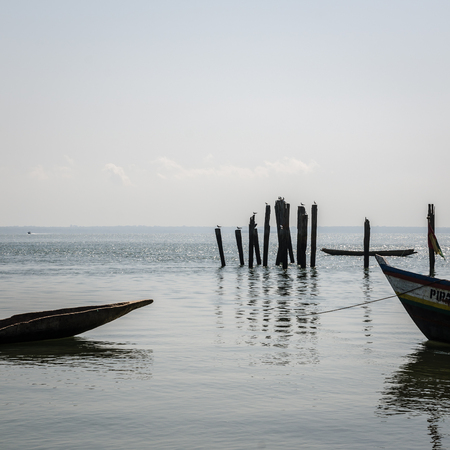 Simple wooden boats moored at timber logs at harbor of Bubaque island, Bijagos Archipelago, Guinea Bissau Reklamní fotografie