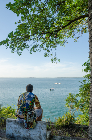Rear view of young man sitting at coast overlooking the ocean wearing colorful african shirt, Bubaque, Guinea Bissau