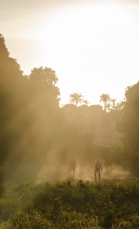 African football game on tropical island Bubaque during sunset with bright light, sun rays and dust, Guinea Bissau
