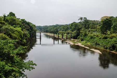 Crumbling iron and concrete bridge crossing Munaya river in rain forest of Cameroon, Africa.
