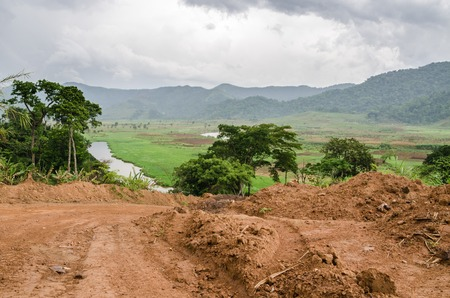 River and dirt road with mountains and lush vegetation, Bamenda Ring Road , Cameroon, Africa.