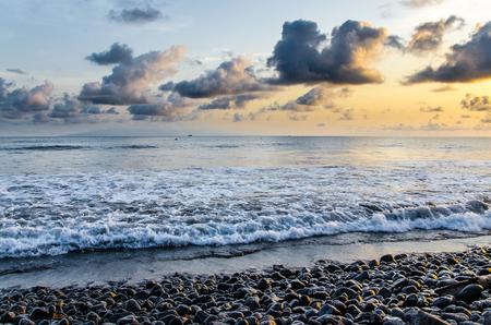 Dramatic coast with rocky volcanic beach, waves and beautiful sunset, Limbe, Cameroon.