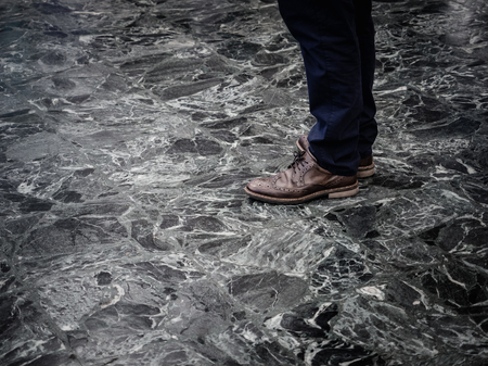Low section of man wearing smart leather shoes standing on marble floor indoors. Reklamní fotografie