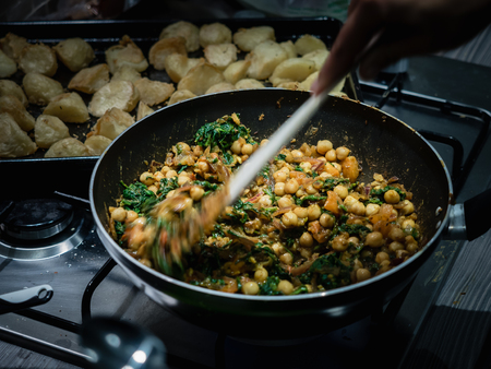 Hand stirring Indian chickpea and spinach curry in wok on gas stove indoors. Reklamní fotografie