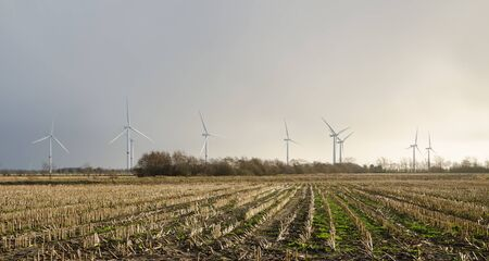 Wind turbines creating electricity out of wind energy on stubble field in rural Germany. Reklamní fotografie