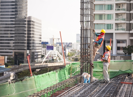 labor placing rebar at construction site