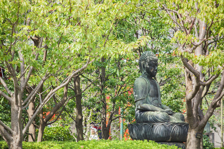 presumption: The buddha sculpture in garden. Sunlight shining through the trees. Stock Photo