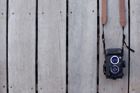 Film camera is old on wooden background.  photo
