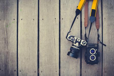 필름 카메라는 나무 배경에 오래되었습니다. 카메라는 35mm 트윈 렌즈 리플렉스입니다. 빈티지 또는 복고 스타일입니다.