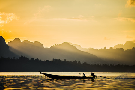 folkways: Fisherman working in morning. Background is mountain and beautiful light of sunbeam. Stock Photo