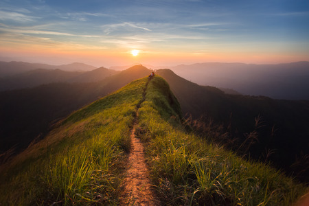 The way of climax. Mountain slope have a way for walk. Background is sunset. Stock Photo