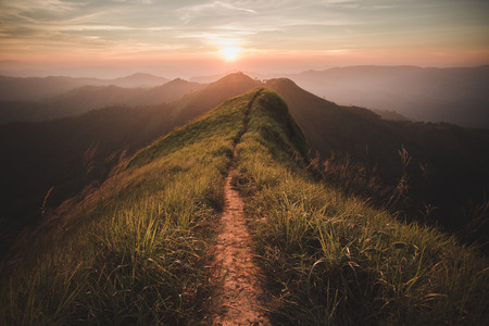 trails: The way of climax. Mountain slope have a way for walk. Background is sunset. Stock Photo