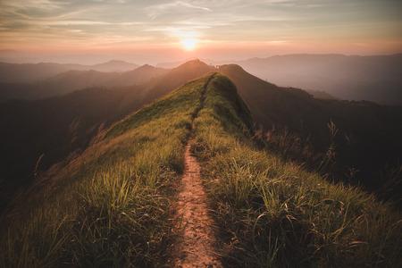 Způsob vyvrcholení. Mountain svahu nechat cestu pěšky. Pozadí je západ slunce.