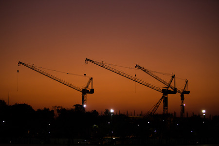 reconstruct: Construction in morning. Sky color is orange. crane is silhouette.
