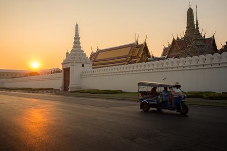 Tuk-Tuk drive on street and background of Wat Phra Kaew in morning.  photo