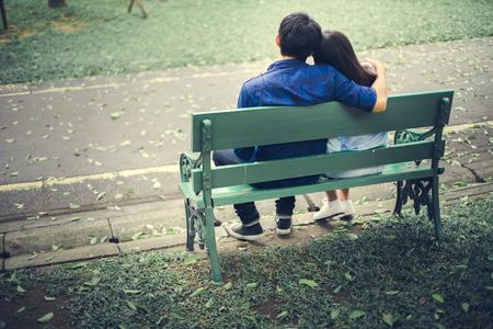 pareja adolescente: Los pares se sientan y abrazar en el jard�n.