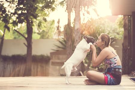 Vrouwen knuffelen een hond en kus. Ze speels en geluk.