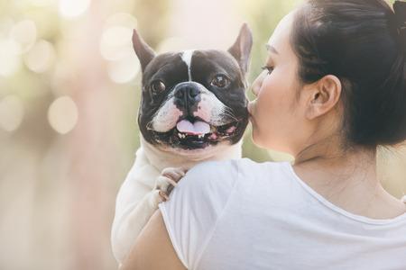 프랑스 불독은 귀여운 키스 소녀입니다. 그녀는 개에 실시한다.
