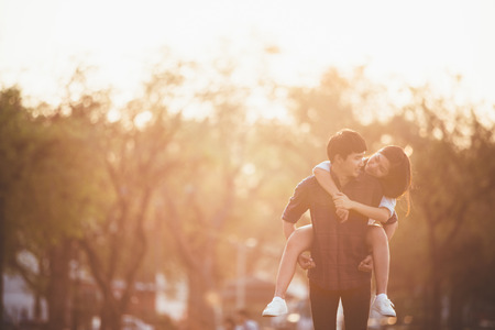 is playful: Novia paseo posterior del novio. Pareja de relax en el jardín de la noche. Sol haciendo cálido y ellos la felicidad. Foto de archivo
